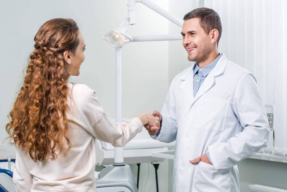dentista cumprimentando sua paciente em seu consultorio. Ele esta olhando para ela e sorrindo . Ela esta de costas para a camera, tem cabelos enrolados e veste uma camisa rosa claro