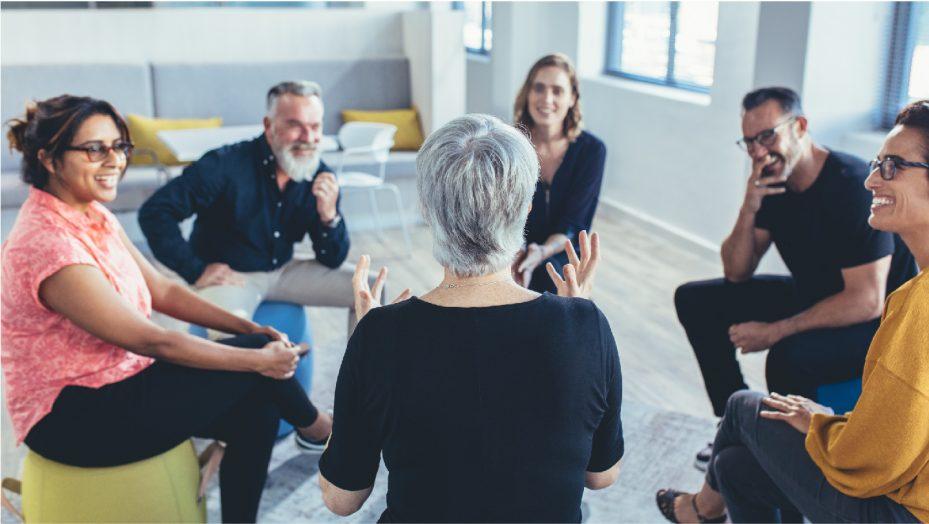 grupo de seis pessoas que trabalham juntas sentadas em circulo, conversando sobre qualidade de vida no trabalho. Elas estão alegres e sorrindo, compartilhando informações
