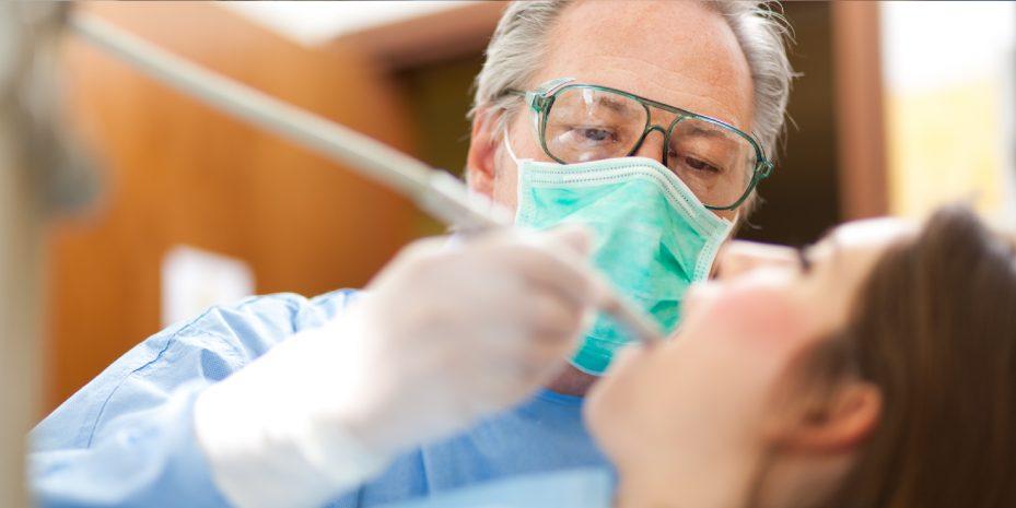 dentista realizando um tratamento em sua paciente. ela esta de boca aberta e ele segurando um instrumento dentro da boca dela