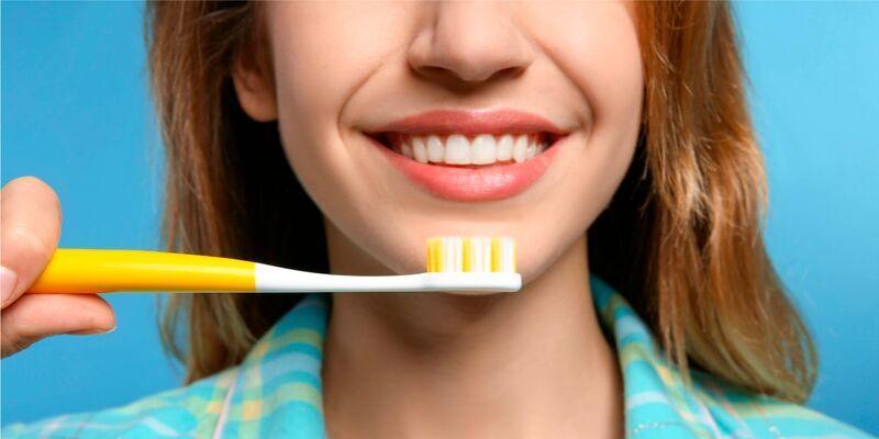 fundo azul com parte do rosto de uma mulher sorrindo. Ela esta segurando uma escova de dente amarela na frente do rosto