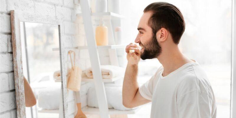 homem se olhando no espelho enquanto esta escovando seus dentes. Ele esta usndo uma camiseta branca e ao fundo é possível ver detalhes do banheiro