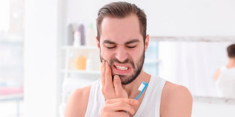 homem sofrendo com uma dor de dente. Ele esta usando uma regata branca, apoiando a mão esquerda na bochecha direita enquanto segura a escova de dente com a outra mão