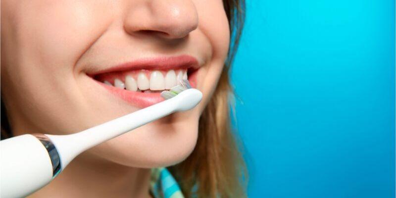 mulher sorrindo e escovando seus dentes com uma escova de dente do tipo elétrica