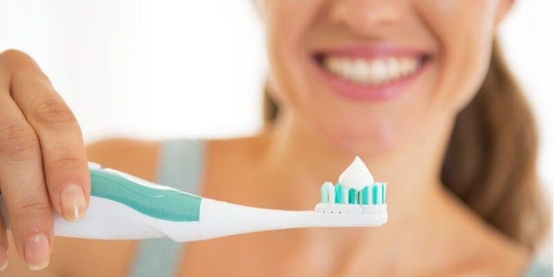 mulher sorrindo e segurando uma escova de dente azul e branca com pasta de dente