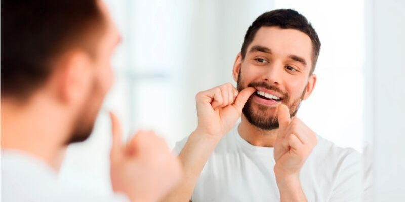 reflexo de um homem se olhando no espelho enquanto passa fio dental nos dentes
