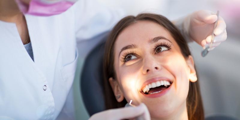 a imagem mostra o rosto de uma paciente que possui plano odontológico empresarial. Ela esta de boca aberta, enquanto a dentista analisa seus dentes