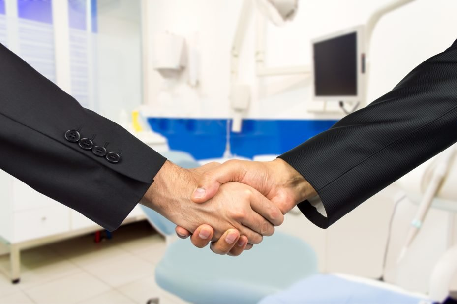 aperto de mãos entre dois empresários fechando um plano odontologico e, ao fundo, pode-se ver uma clinica odontologica