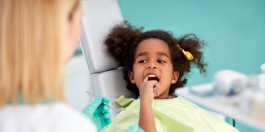 criança sendo atendida por meio do plano odontologico infantil. ela esta de boca aberta e olhando diretamente para a dentista