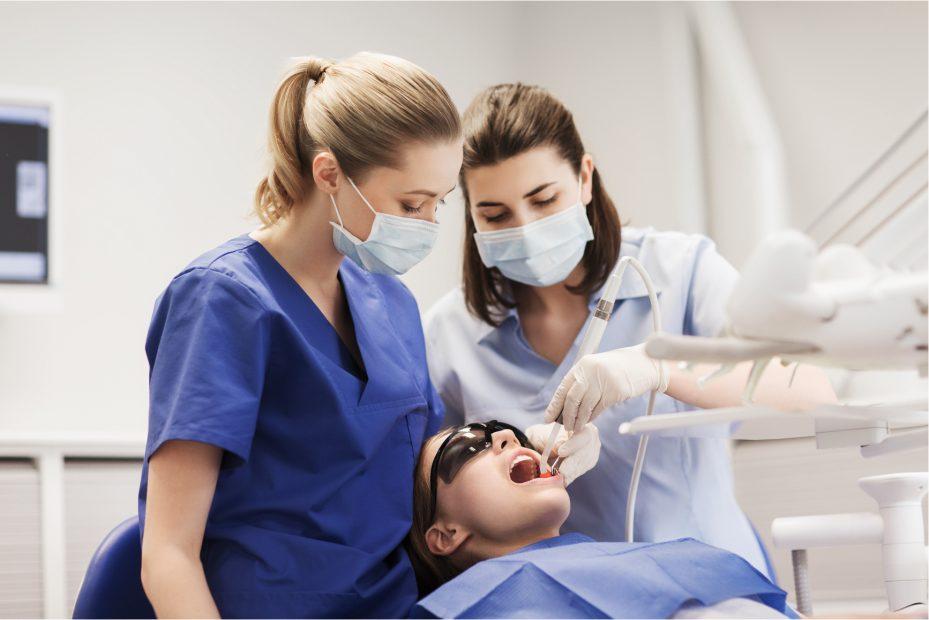 dentista e assistente durante atendimento de sua paciente. A menina esta deitada na cadeira de dentista, com a boca aberta