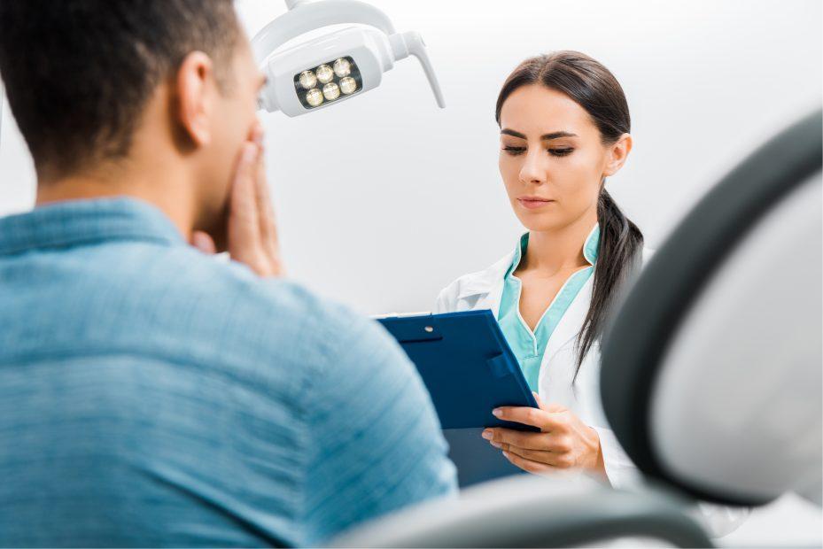 dentista examinando um paciente que deseja saber se plano odontologico cobre extraçao de siso. Ele esta de costas para a camera, com a mão apoiada sobre a bochecha, com dor no dente