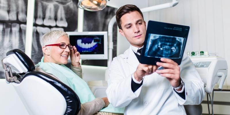 dentista segurando um exame de raio x para sua paciente ver. Ela esta sentada na cadeira do consultorio e usa oculos de armação vermelha para enxergar