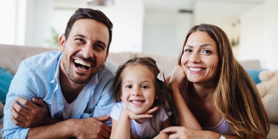família formada pelo pai, mãe e uma filha. Eles estão deitados, de bruço, apoiados nos braços e sorrindo para a camera