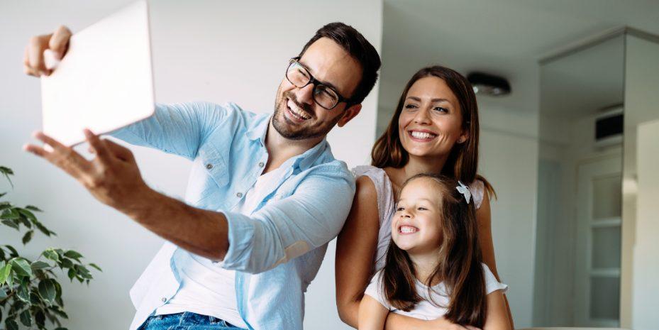 familia formada pelo pai, mae e filha tirando uma foto. o pai esta segurando um tablet e todos estão sorrindo em direção a foto
