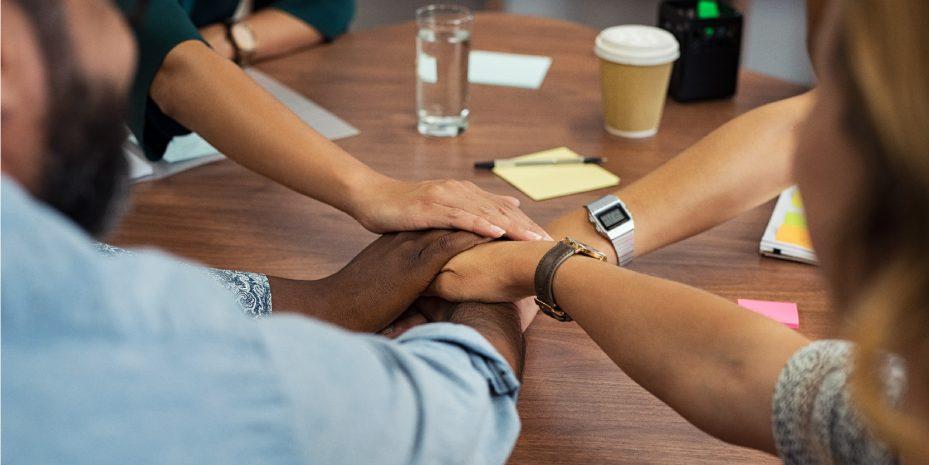grupo de colaboradores unindo as mãos em cima de uma mesa de reunião