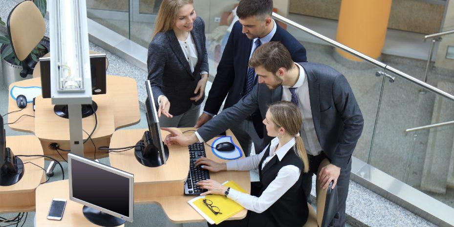 grupo de quatro jovens empresarios trabalhando. Uma mulher esta sentada em frente ao computador, dois homens estão sorrindo e olhando para a tela e uma outra mulher também
