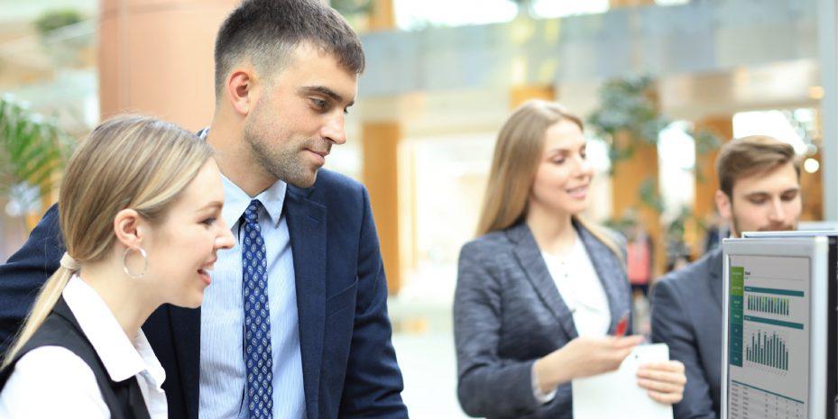 homem e mulher olhando para alguns índices em uma tela de computador. ao fundo pode-se ver um homem e uma mulher olhando outros dados em papeis
