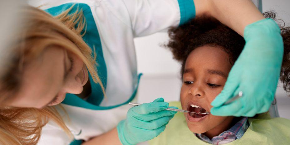 menina sendo atendida por sua dentista. ela esta de boca aberta enquanto a profissional analisa seus dentes com um instrumento em cada mão