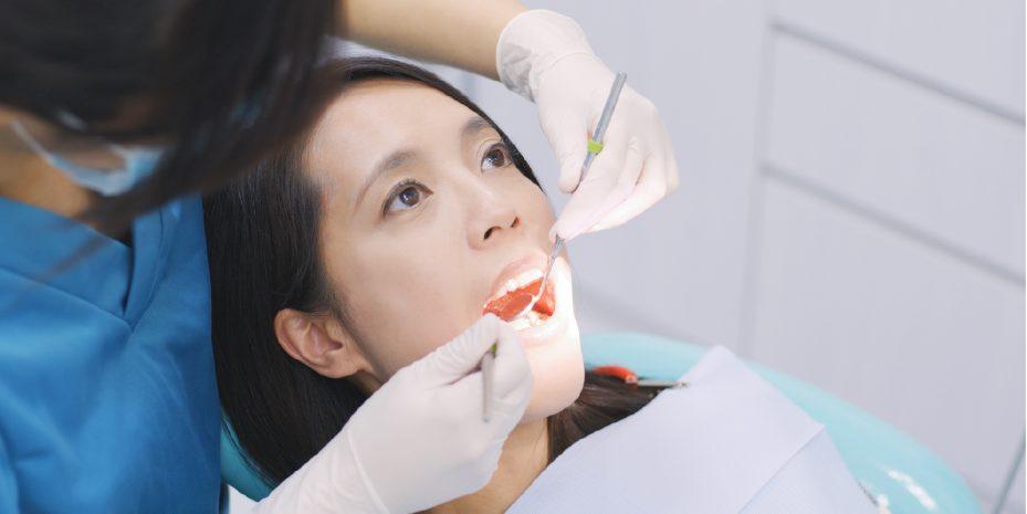 mulher deitada na cadeira de sua dentista de boca aberta. tem uma luz em direção a boca dela e a dentista esta analisando seus dentes
