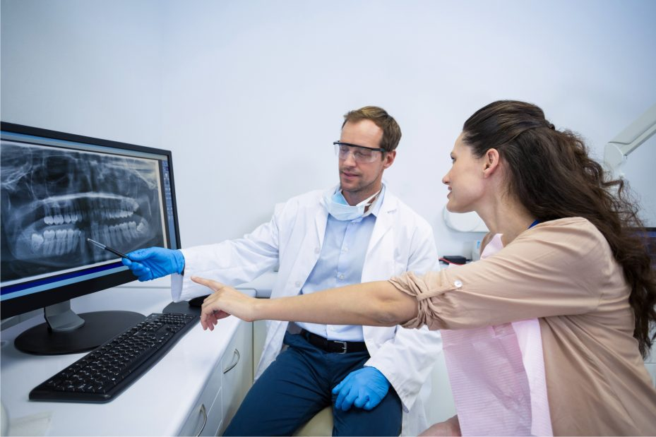 mulher e seu dentista analisando um raio x. Ela esta apontando para o exame, enquanto seu dentista olha para a tela do computador e analisa