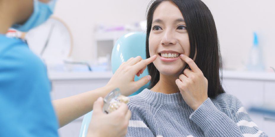mulher japonesa durante atendimento do seu plano odontologico bom e barato olhando para a sua dentista, sorrindo e apontando para a sua boca