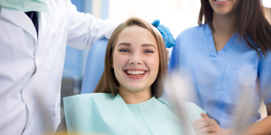 mulher loira em um consultório de dentista, ela está olhando diretamente para a câmera e sorrindo