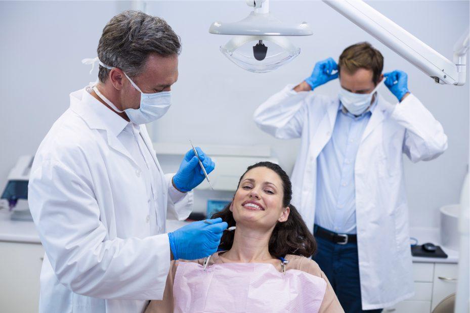 mulher sendo atendida por dois dentistas em um consultorio. Ela esta usando uma blusa rosa claro e esta sorrindo na direção da câmera