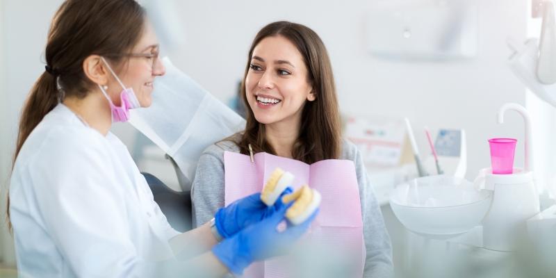 paciente de cabelos morenos olhando para sua dentista e sorrindo, após ser atendida. a dentista usa luvas azuis e está segurando um molde com formato de uma arcada dentaria