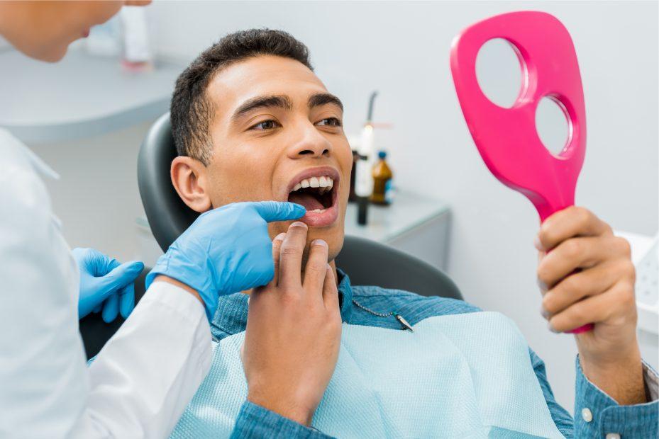 paciente deitado na cadeira de dentista com a boca aberta, segurando um espelho rosa. A dentista esta usando luva, apontando para um de seus dentes
