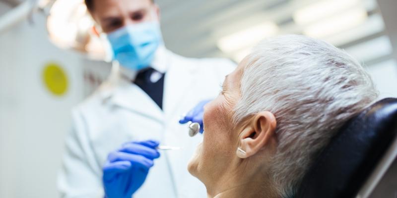paciente mulher de cabelos curtos e grisalhos sendo atendida pelo seu dentista de um dos convenios odontologicos disponiveis no mercado