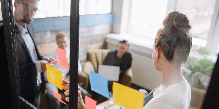 reunião de uma empresa sobre benefícios empresariais. Uma mulher está apontando para alguns post its que estão colados em uma divisória de vidro, enquanto outras três pessoas olham para ela