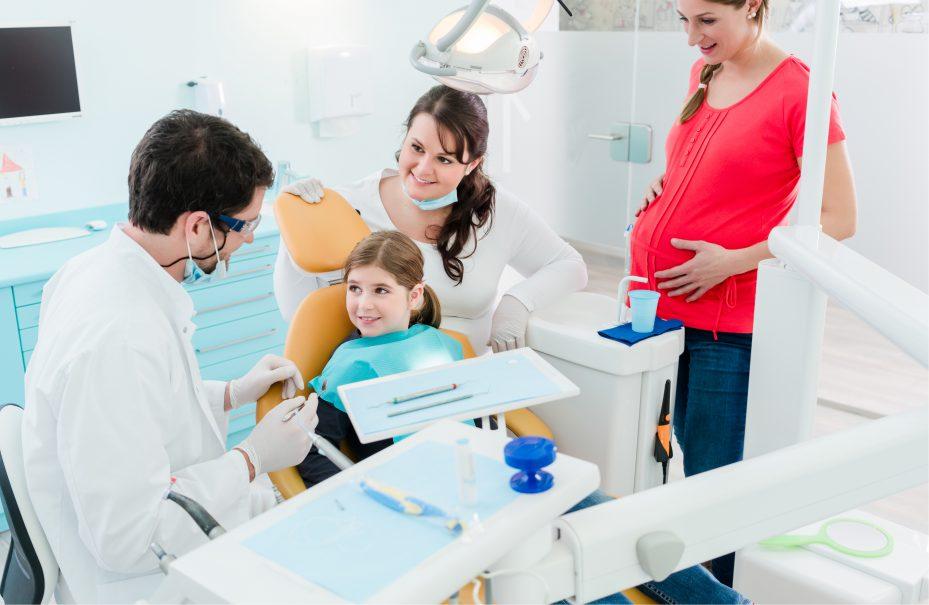 dentista atendendo uma menina enquanto sua mãe, grávida, está ao lado acompanhando o atendimento