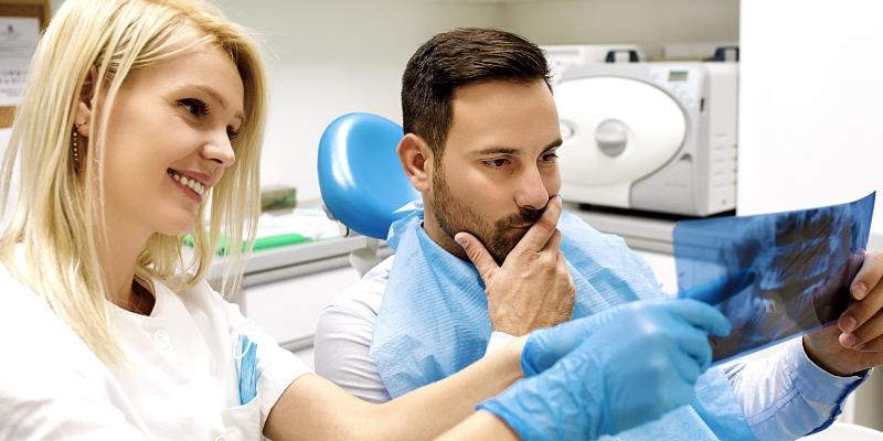 dentista mostrando para seu paciente o resultado de um exame realizado atraves do plano odontologico sem carencia