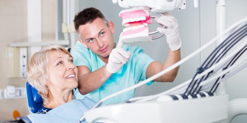 dentista mostrando para sua paciente uma arcada dentária. Ela esta sentada na cadeira de dentista, depois de ser atendida pelo profissional