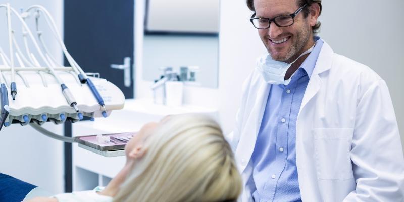 dentista olhando e sorrindo para sua paciente durante o atendimento odontológico