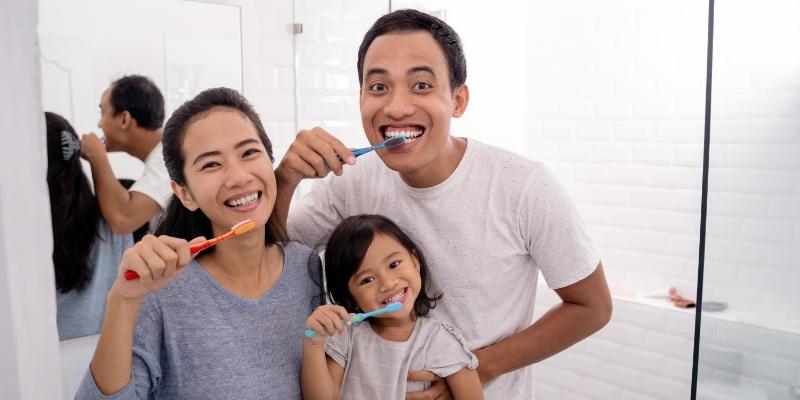 família formada por pai, mãe e filha felizes enquanto escovam os dentes antes da consulta do convenio odontologico familiar