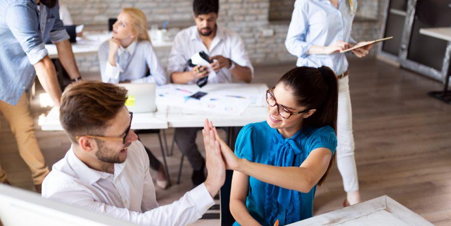 homem e mulher tocando as mãos em sinal de vitória. Eles estão em seu ambiente de trabalho