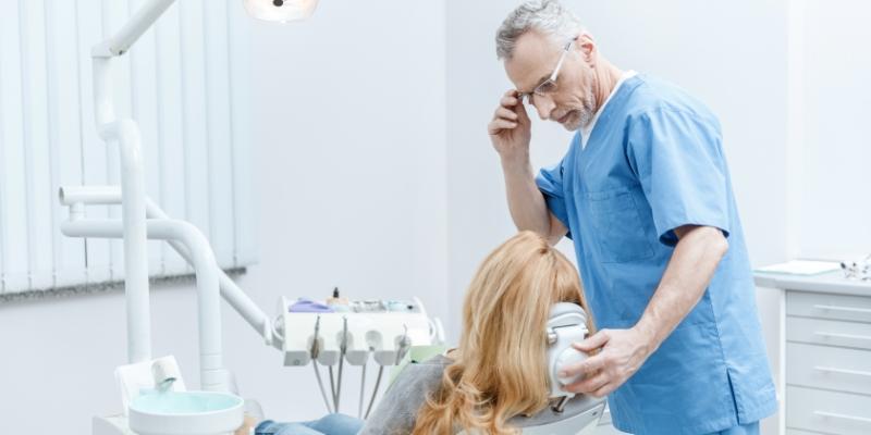 mulher de cabelos loiros sentada na cadeira de dentista, de costas para a camera, sendo atendida pelo seu dentista para o tratamento para gengivite