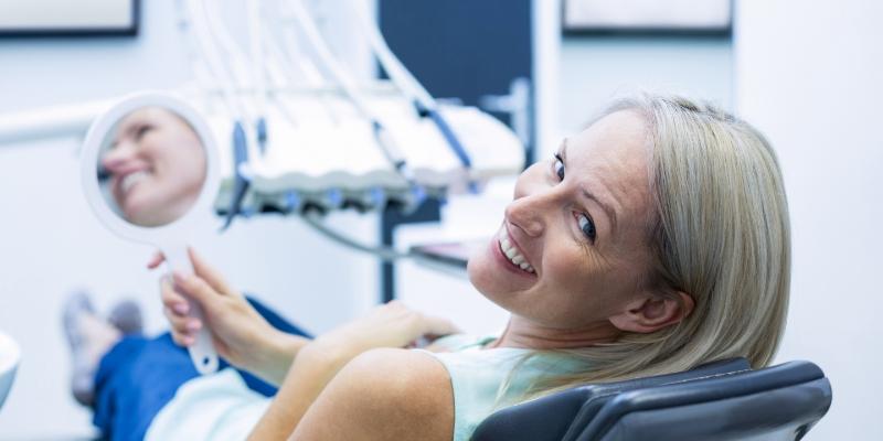 mulher loira olhando para a camera e sorrindo. Ela esta sentada em um consultorio e segurando um espelho de mão para ver seus dentes