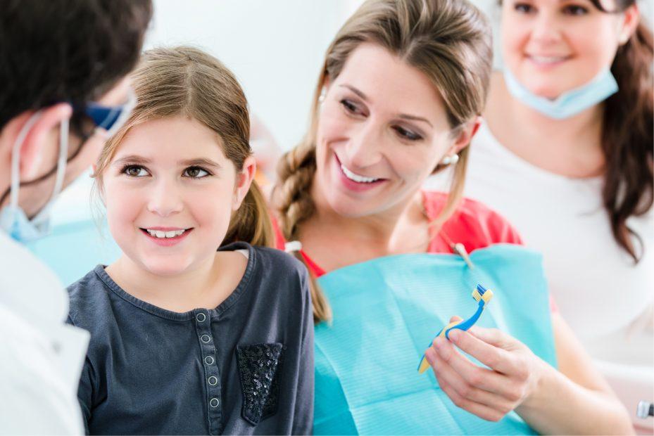 mulher sendo atendida pelo seu dentista e assistente. Ela esta segurando uma escova de dente para dar para sua filha