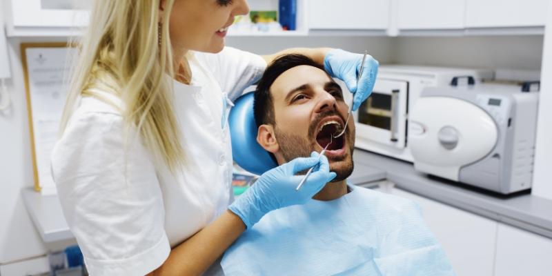 paciente sentado na cadeira de dentista com a boca aberta. Ele esta sendo examinado pela sua dentista