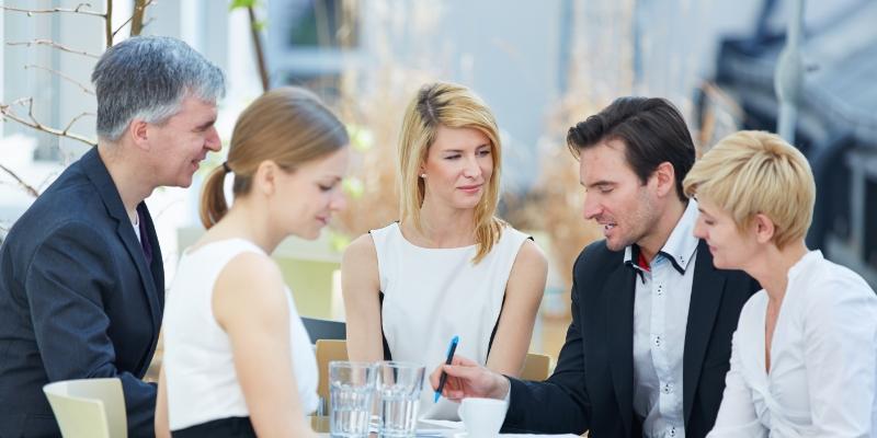 foto de três pessoas sentadas em círculo escutando um homem de terno preto falar sua ideia para reter talentos para sua empresa