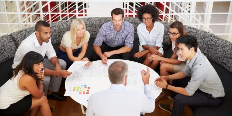 várias pessoas sentadas em um sofá formando um círculo escutando um homem falar sobre a diminuição do turnover