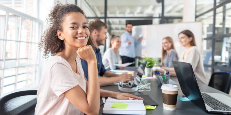 Seis pessoas reunidas em uma sala do escritório, mesa com cadernos e computadores. Homem com blusa azul explicando estratégias para reter talentos e mulher sorrindo com a mão no queixo