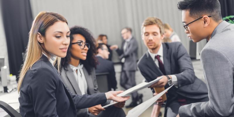 quatro pessoas reunidas em um escritório e segurando papéis nas mãos debatendo como aumentar a retenção de colaboradores na sua empresa