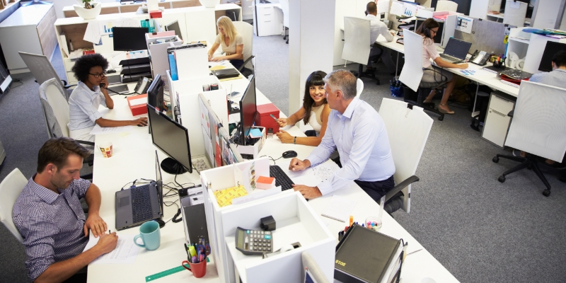várias pessoas sentadas em suas mesas com computadores e telefones num escritório, homem sentado do lado de uma mulher mostrando na tela do computador como realizar a diminuição do turnover
