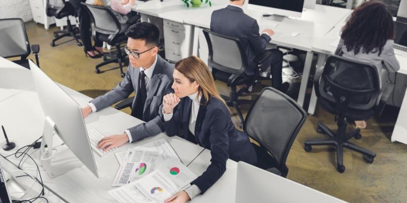 duas pessoas sentadas de frente para uma mesa com computador elaborando estratégias para aumentar a retenção de colaboradores