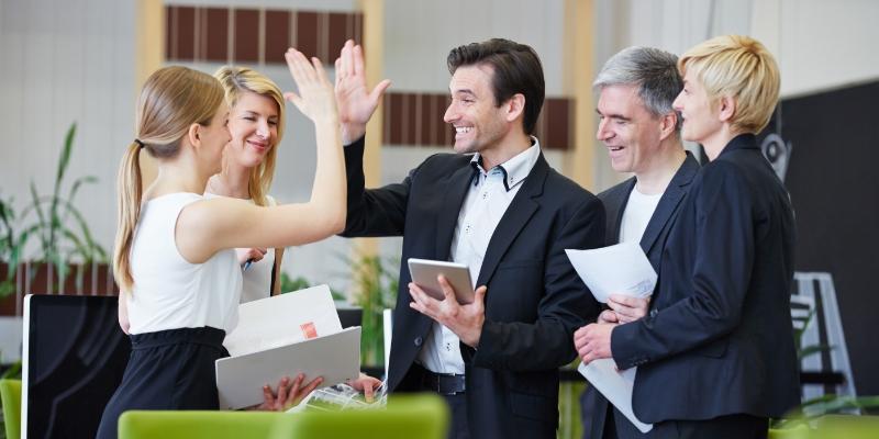 cinco pessoas em circulo comemorando após definir suas estratégias para reter talentos, uma mulher loira de cabelo amarrado está batendo a mão de um homem de terno preto com um tablet na mão