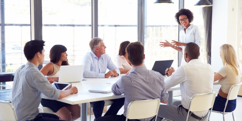 várias pessoas sentadas em uma sala de reunião escutando uma mulher falar sobre a diminuição do turnover