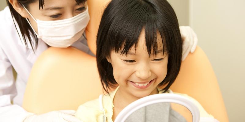 criança oriental sorrindo deitada em uma cadeira de dentista em um consultório de odontopediatria enquanto o dentista realiza exames