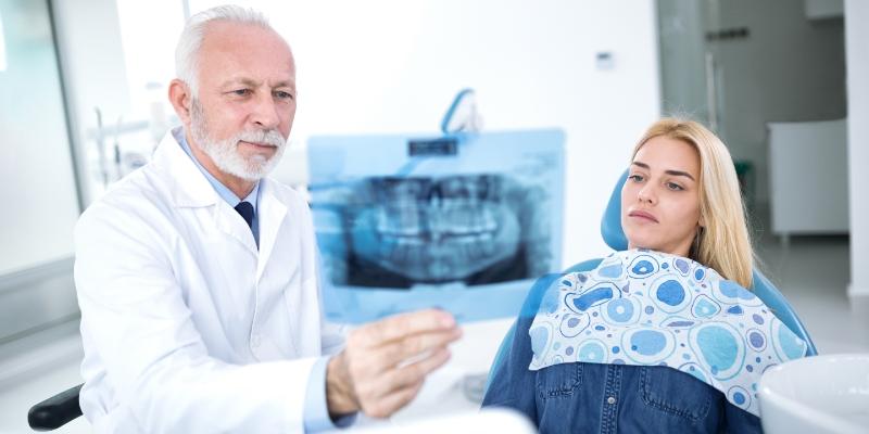 Mulher loira em um consultório deitada vendo um exame que o dentista está mostrando, pois está com nevralgia dentária